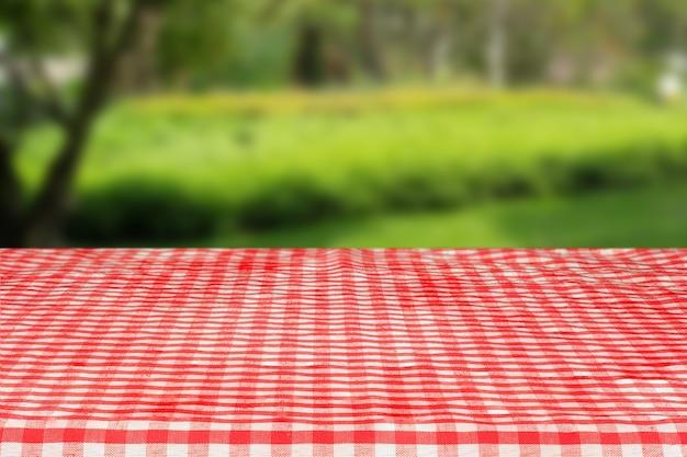 정원에서 추상 녹색 보케가 있는 빨간색 체크 무늬 식탁보 질감 상단 보기
