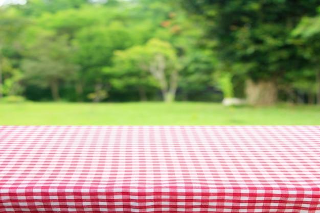 庭から抽象的な緑のボケ味と赤い市松模様のテーブルクロスのテクスチャ上面図