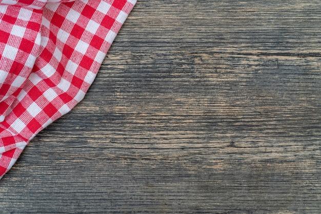 Красное клетчатое полотенце на кухонном столе. предпосылка деревянного стола.