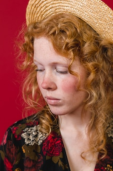 Red cheeked ginger young woman looking down