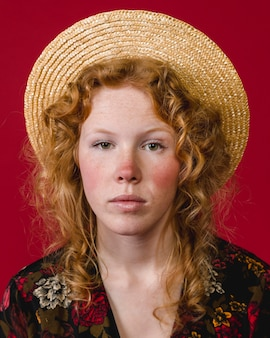Red cheeked young ginger woman looking at camera