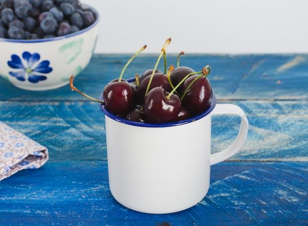 Красные вишни и клюквы в белом шаре на деревянной предпосылке. Premium Фотографии