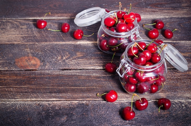Red cherries in a glass jar on dark wooden background with copy space. sunny summer and harvest concept.