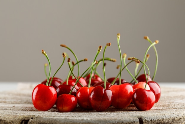 Red cherries on grey and wooden board surface. side view.