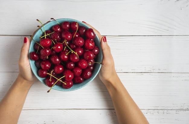 Красные вишни в декоративной синей миске в руках человека