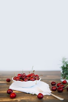 Red cherries in bowl on wooden table top