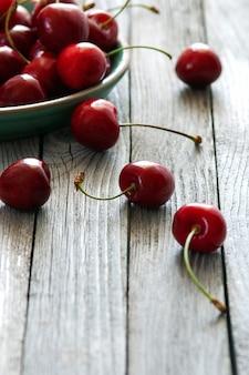 Красная вишня в керамической тарелке на деревянном столе