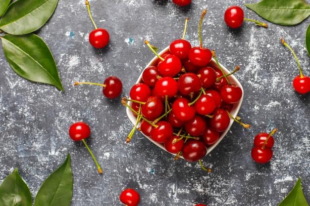 灰色のテーブルの上の皿のボウルに赤いサクランボ