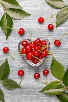 Красная вишня в прозрачной стеклянной миске на сером столе