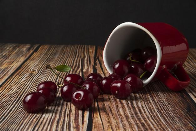 Ciliegie rosse da una tazza bianca sul tavolo