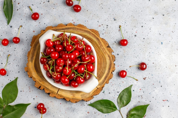 Red cherries in plate bowl on gray table
