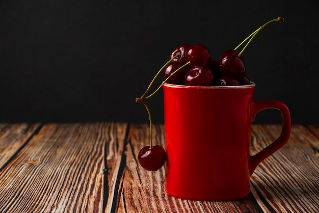 Red cherries in a red cup on the table
