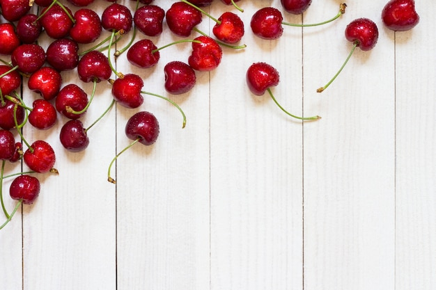 Red cherries on white wood