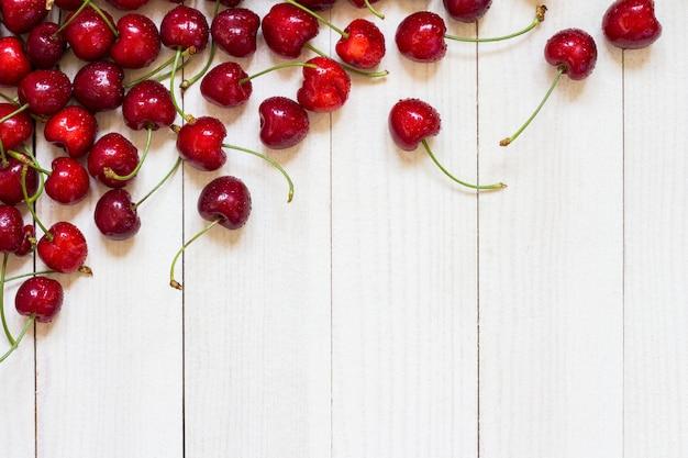 Ciliegie rosse su legno bianco