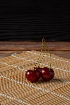 素朴なマットに緑の茎を持つ赤いサクランボ