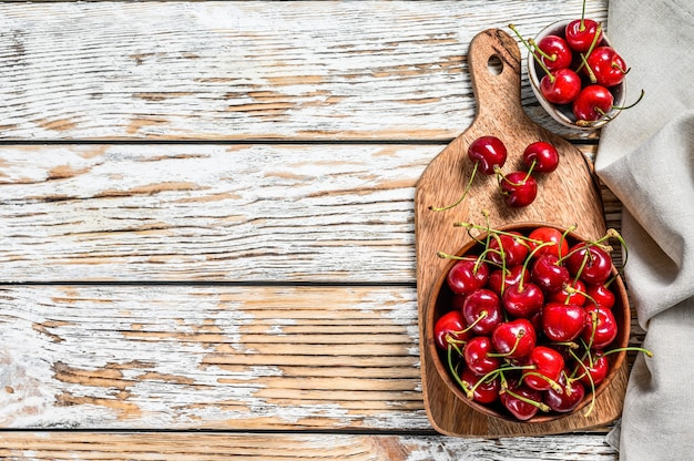 Red cherries in a wooden bowl. white background. top view. copy space.