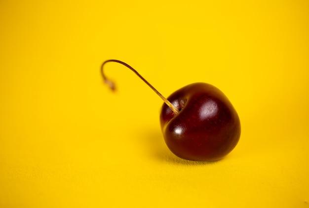 Красная вишня крупным планом на желтом фоне