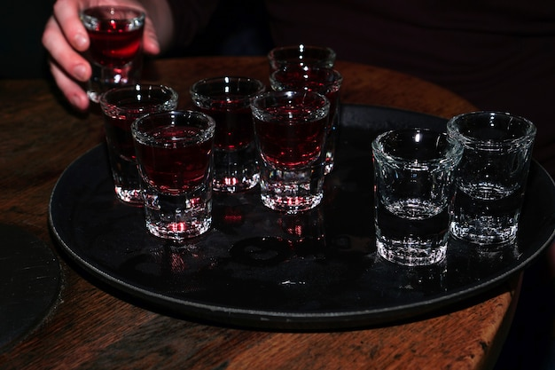 Red cherry drink in shot glasses with hands - party in bar