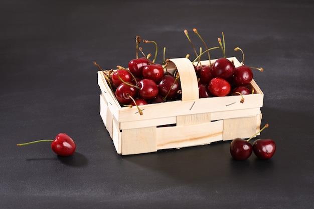 Красная вишня в плетеной корзине на темном фоне
