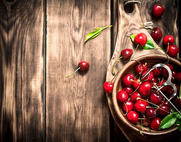 カップの赤いチェリーとチェリー用の金属製の道具。木製のテーブルの上。