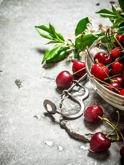カップの赤いチェリーとチェリー用の金属製の道具。石のテーブルの上。