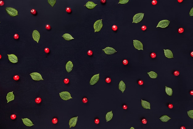 Red cherry pattern with green leaves on black wooden background