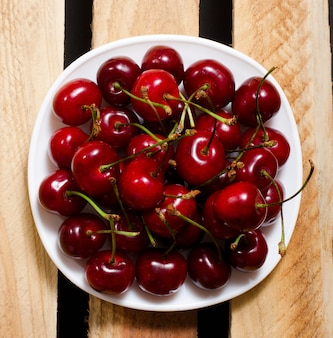 Red cherry in a plate on wooden boards, top view