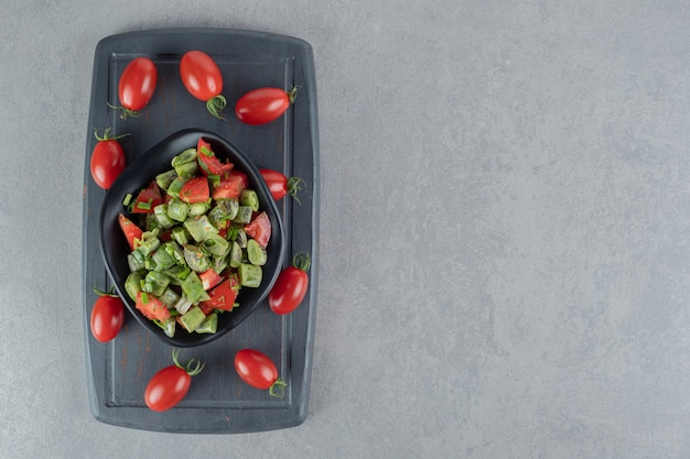 Red cherry tomato and beans salad on a black wooden board