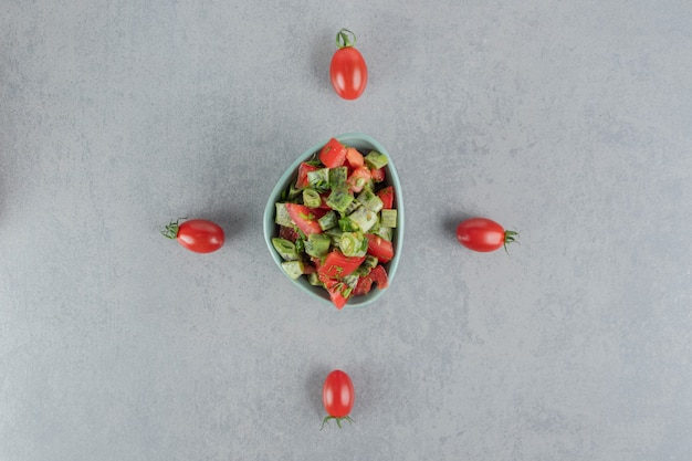 Red cherry tomato and beans salad in a blue cup