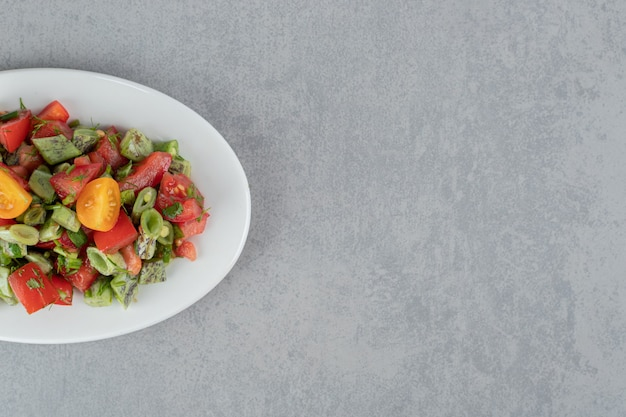 Red cherry tomato and beans salad in a ceramic plate