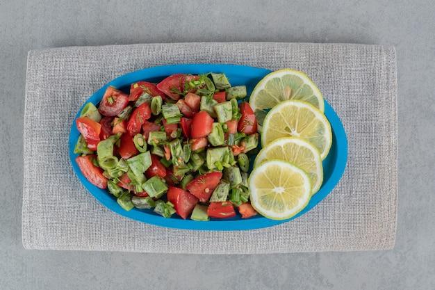 大皿にガラスのカップに赤いチェリートマトとインゲンのサラダ。