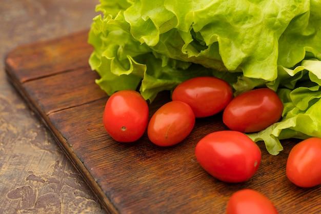 古いまな板に赤いチェリートマトとグリーンサラダ。ダイエット食品