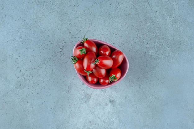 Red cherry tomatoes in a cup on blue.