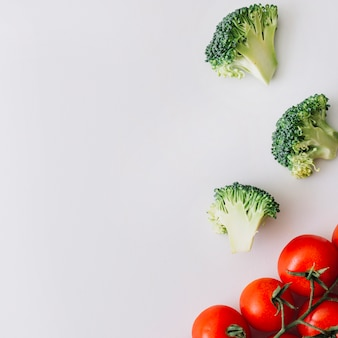 Red cherry tomatoes and fresh broccolis slices against white backdrop