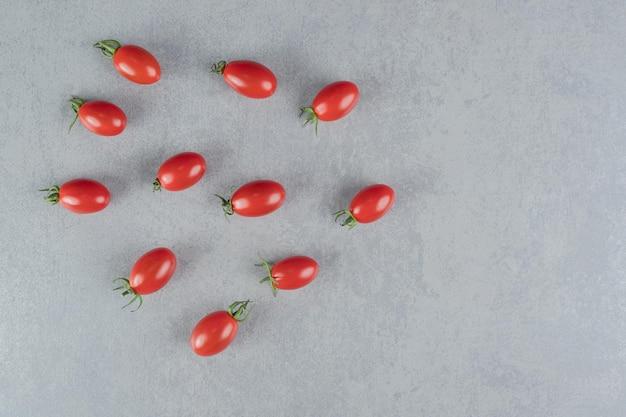 Pomodorini rossi isolati su un tavolo di cemento.