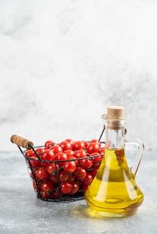 대리석 테이블에 엑스트라 버진 올리브 오일 한 병과 빨간 체리 토마토.