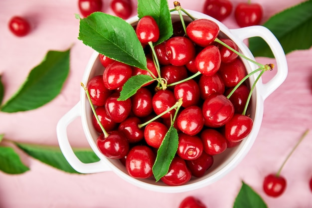 Red cherry in white bowl on pink .
