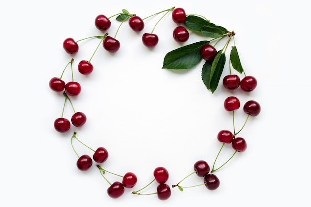 Red cherry with petioles lined in a frame with green leaves. concept of vegetarianism and love of nature. fruit frame. fruit diet copies save