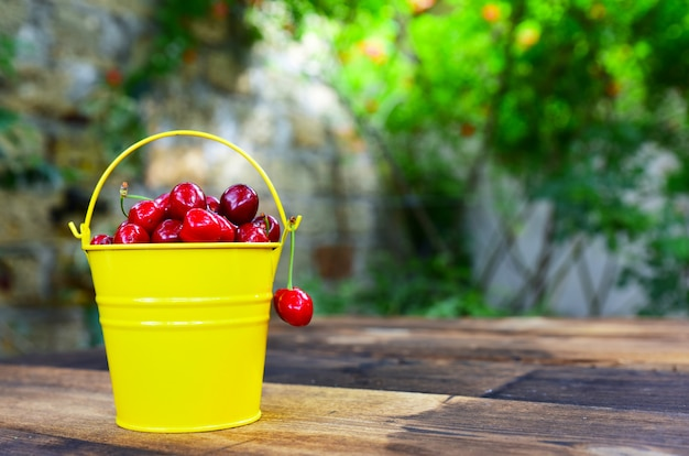 Red cherry in a yellow bucket on a brown wooden table