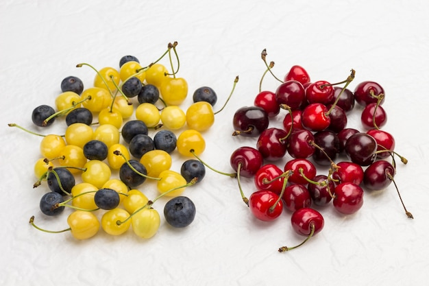 Red cherry, yellow cherry and blueberry on white surface
