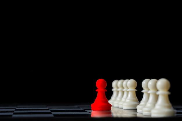 Красный шахмат стоя вне от белых шахмат на шахматной доске и черной предпосылке. концепция лидерства.