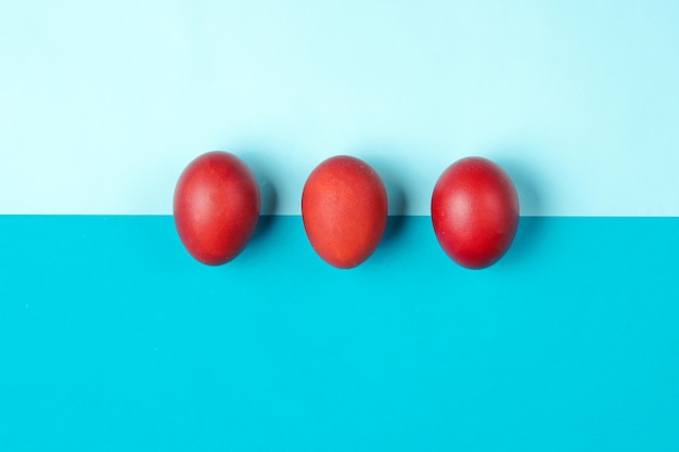 Red chicken eggs on color paper table. minimalistic easter concept