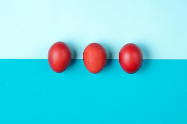 カラーペーパーテーブルに赤い鶏の卵。ミニマルなイースターのコンセプト