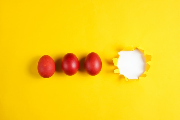Red chicken eggs on a yellow paper table with a torn hole minimalism easter concept