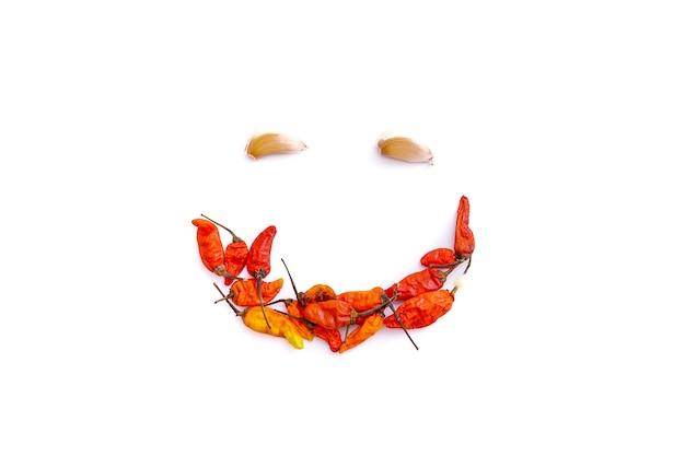 Красный перец чили и чеснок, чтобы сформировать улыбающееся лицо, изолированное от белого