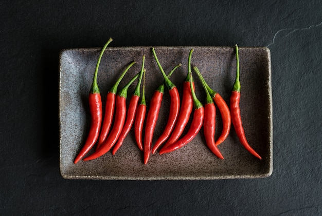 Red chili pepper on black background, top view