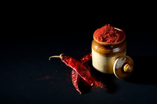 Red chili pepper powder in clay pot with red chili peppers on black surface