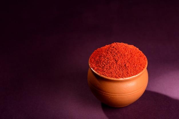 Порошок красного перца чили в глиняном горшочке