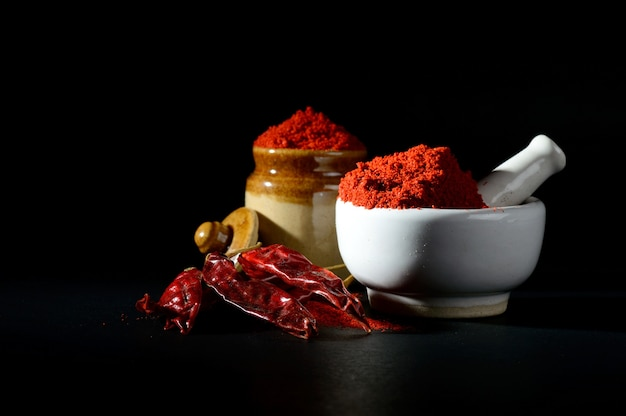 Red chili pepper powder in pestle with mortar and clay pot with red chili peppers on black surface