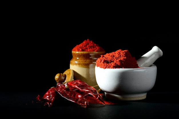 Red chili pepper powder in pestle with mortar and clay pot with red chili peppers